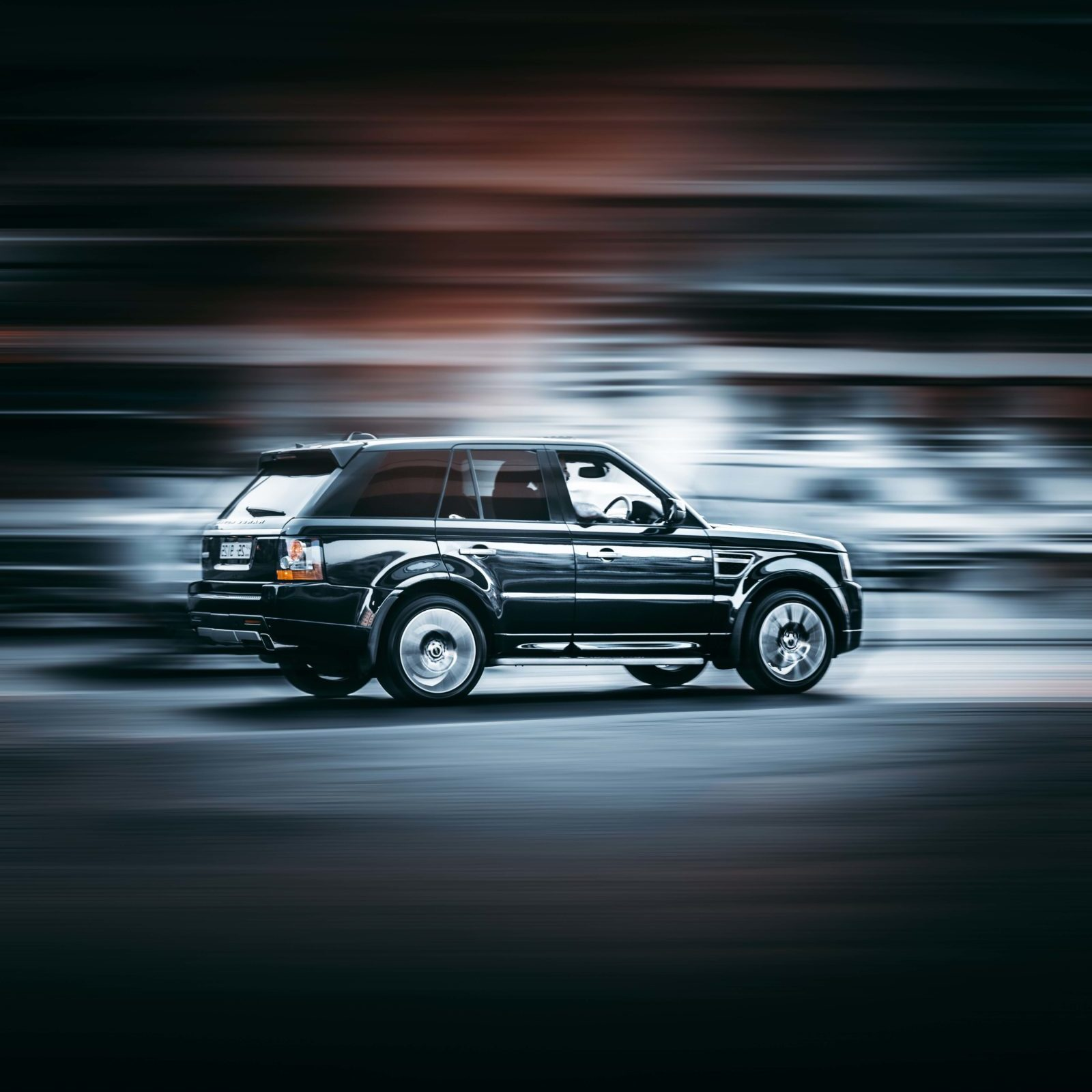 Range Rover driving towards the right. The background is blurred.